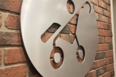 Custom solid brushed aluminium circular logo raised fro mthe wall