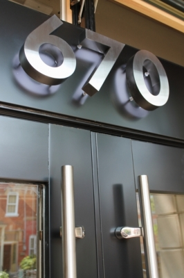 Brushed fabricated stainless steel numbers LED illuminated from behind.