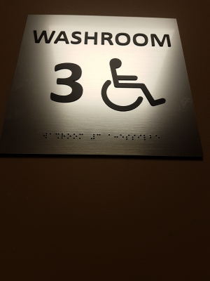 interior washroom sign with raised text and braille
