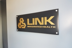 Reception sign brushed gold 3D letters on aluminium panel installed raised from the wall for LINK