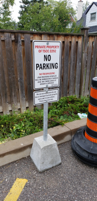 Custom-parking-sign-with-concrete-base-and-post