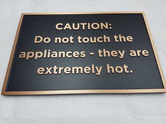 Custom bronze plaque with raised text Caution
